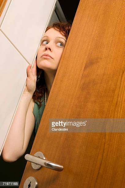 Young woman peeking through door, close-up