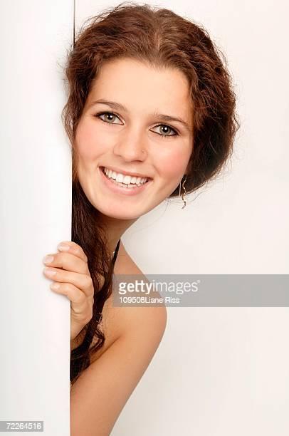 Young woman peeking through door, portrait, smiling