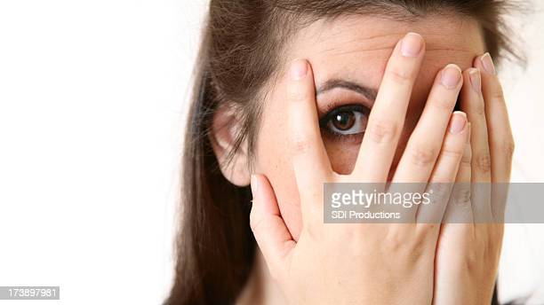 Young Woman Peeking Through Her Fingers, With Copy Space