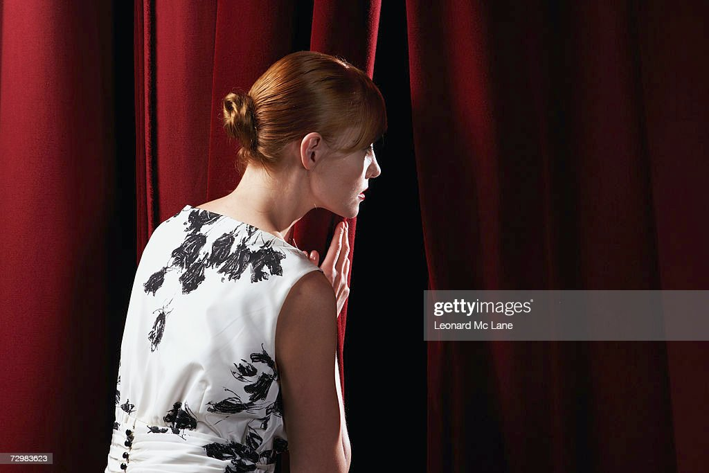 Young woman peeking through stage curtain : Stock Photo