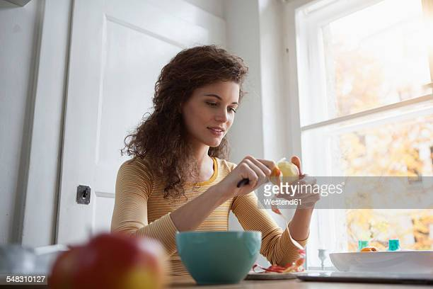 Young woman peeling an apple