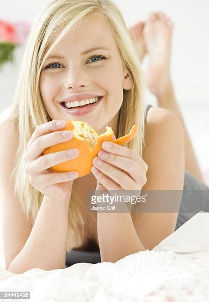 Young woman peeling an orange in bed