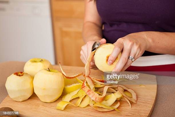 Young Woman Peeling Apples in Kitchen
