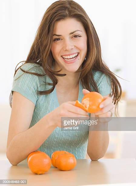 Young woman peeling clementine, smiling, portrait, close-up