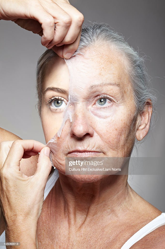 Young woman peeling off old mask : Stock Photo