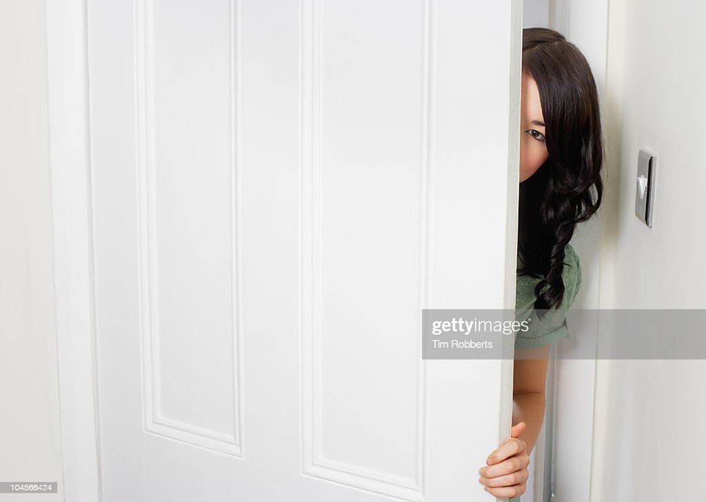 Young woman peering out from behind door.