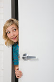 Young woman peering through doorway, smiling
