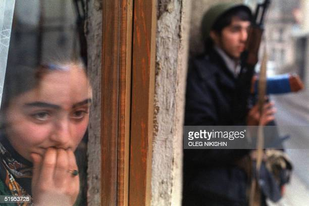 A young woman peers out a window in Tbilisi 29 December 1991 as an armed opposition member stands on guard outside Fierce fighting has continued...
