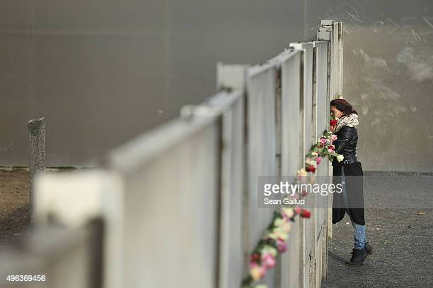 A young woman peers through concrete slats among flowers left by other visitors at the Berlin Wall memorial at Bernauer Strasse on the 26th...