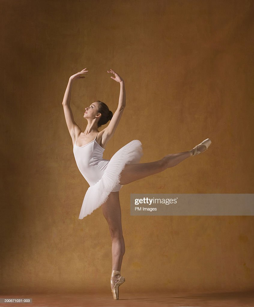 Young woman performing ballet pose, looking up : Stock Photo