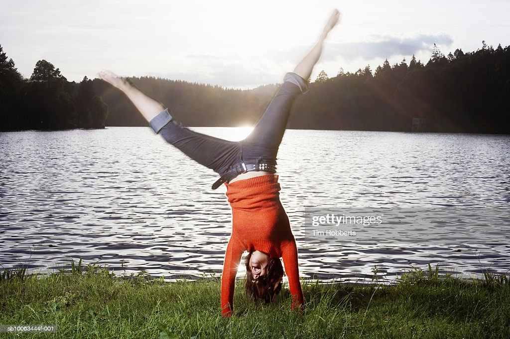 Young woman performing cartwheel by lake : Stock Photo