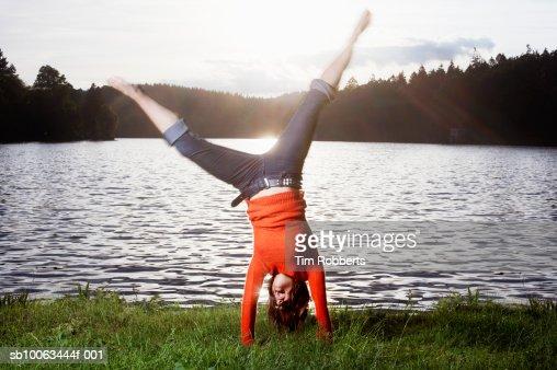 Young woman performing cartwheel by lake : Foto de stock