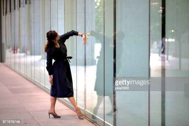 建物のミラーでダンスのポーズを実行する若い女性