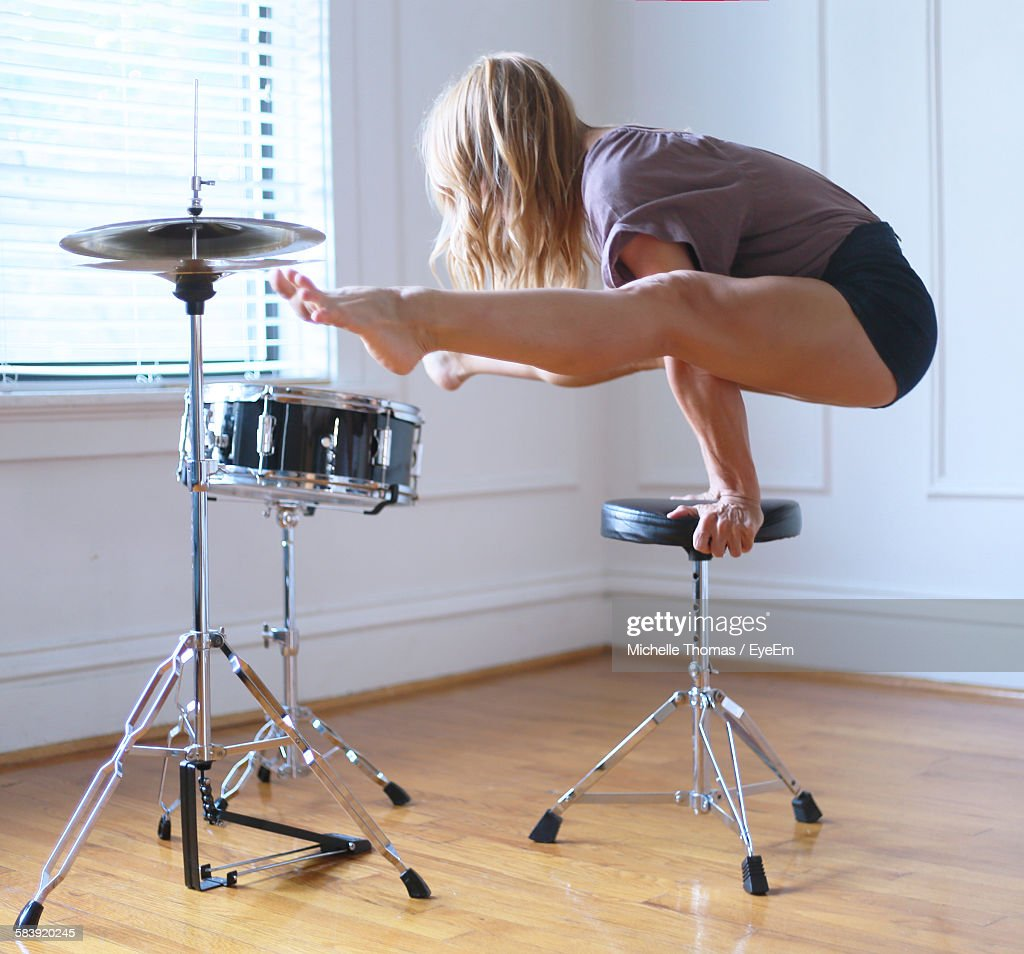 Young Woman Performing Handstand On Seat By Drum Kit At Home