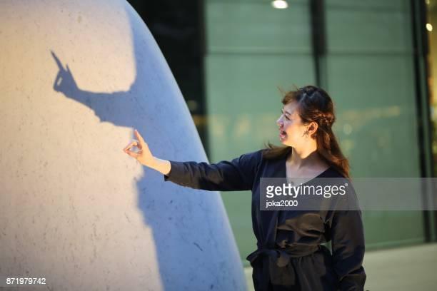 石のオブジェでシルエットを実行する若い女性