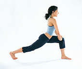Young woman performing stretching exercise, side view