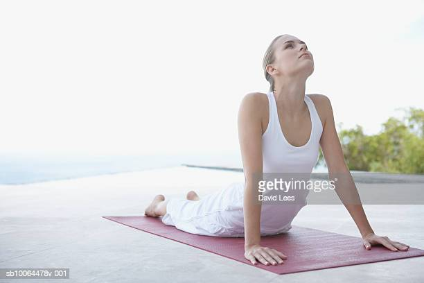 Young woman performing yoga on beach