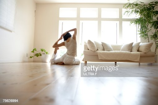 Young woman performing yoga pose in living room : Foto de stock