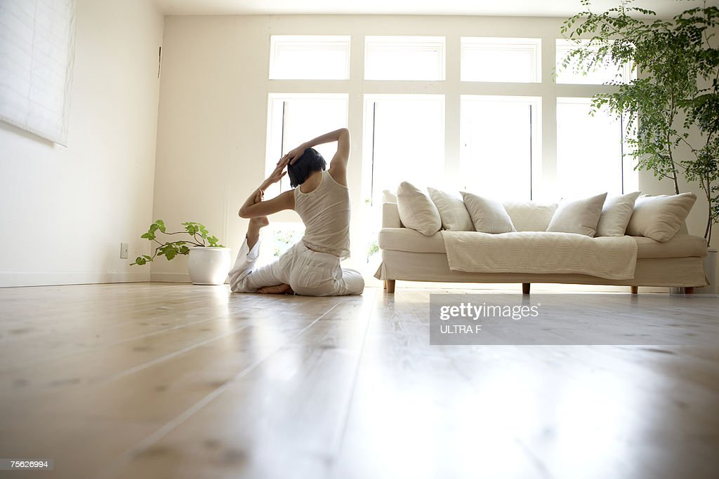 Elegant Young Woman Performing Yoga Pose In Living Room : Stock Photo