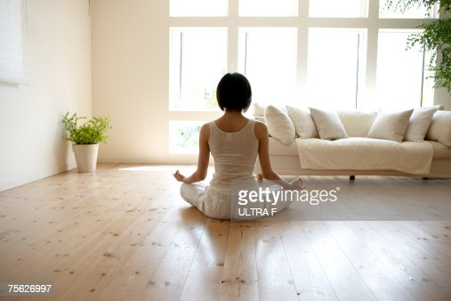 Young woman performing yoga pose in living room : Stock Photo