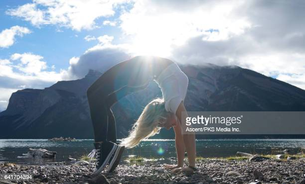 Young woman performs back arch on shore of mountain lake