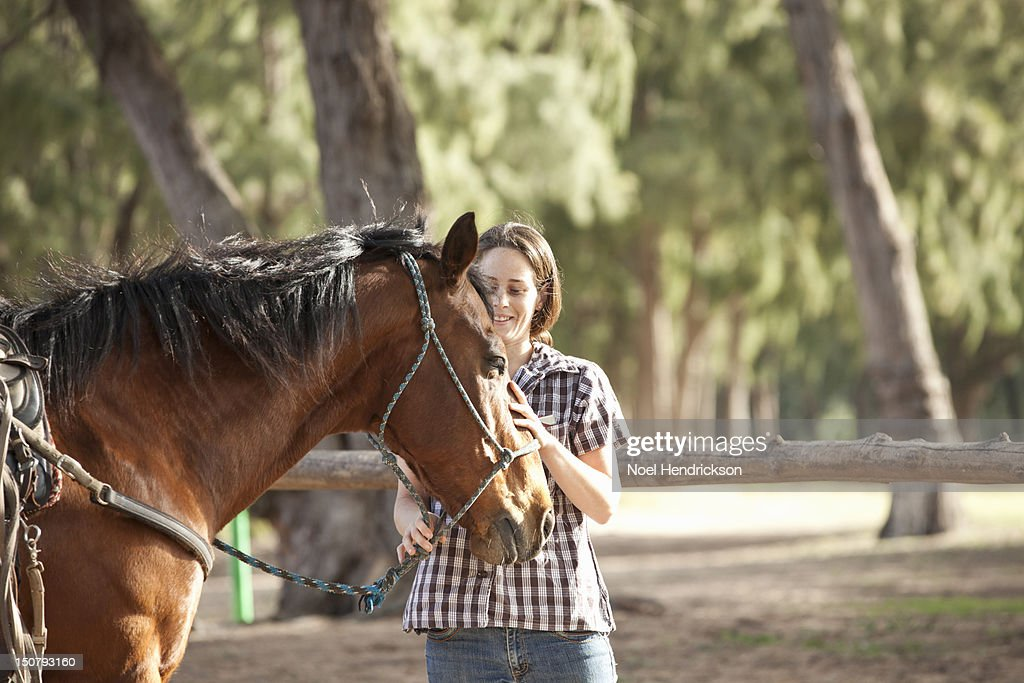 A young woman pets a horse : Stock Photo