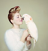 Young woman petting cockatoo, portrait (brightly lit)