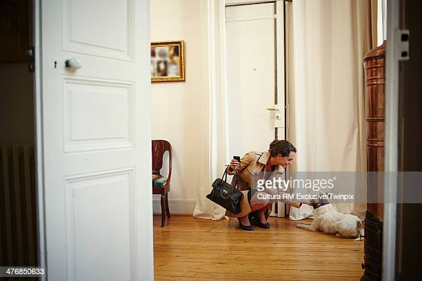 Young woman petting dog on return to apartment