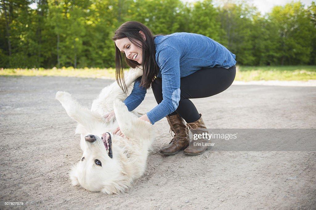 Young woman petting golden retriever on roadside