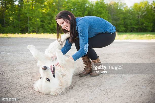 Young woman petting golden retriever on roadside