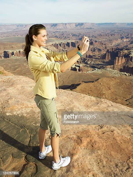 Young woman photographing at rock strata