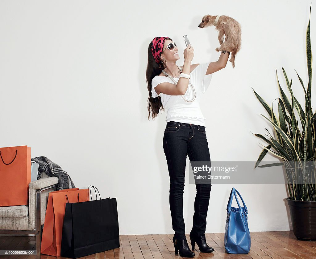 Young woman photographing Cain Terrier dog with mobile phone camera indoors : Stock Photo