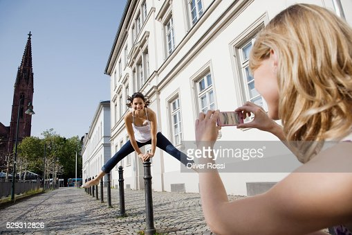 Young woman photographing friend jumping : Stock-Foto