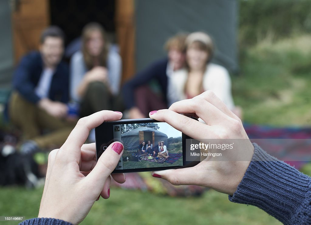 Young woman photographing friends outside yurt. : Stock Photo