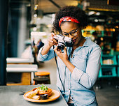 Young African woman standing alone at a counter in a bistro taking photos of her food with a vintage slr camera