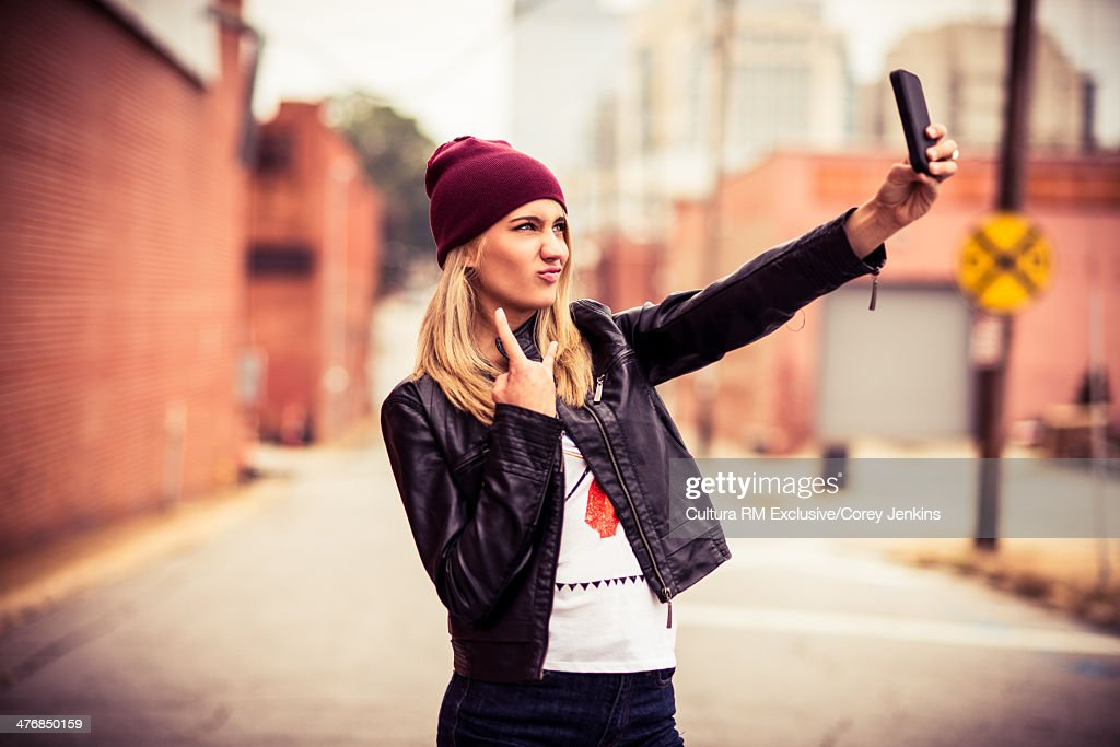 Young woman photographing herself : Stock Photo