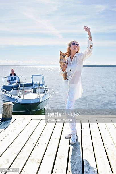 Young woman photographing herself with dog on pier, Gavle, Sweden