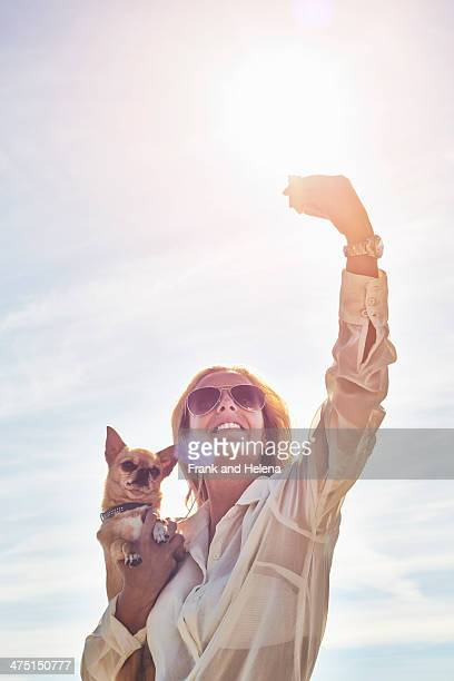 Young woman photographing herself with dog