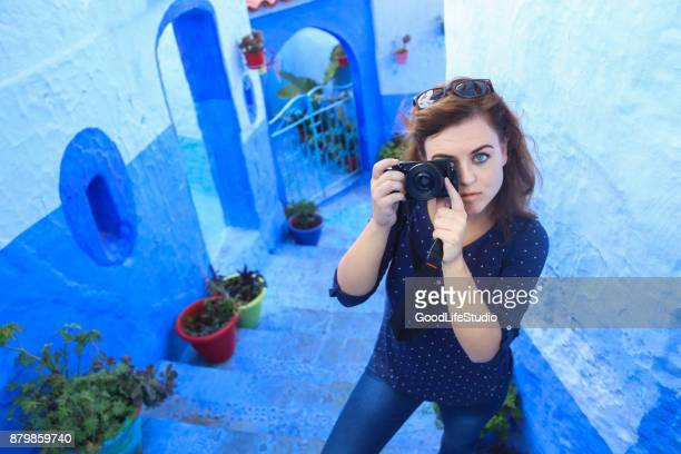 Young woman photographing in Chefchaouen