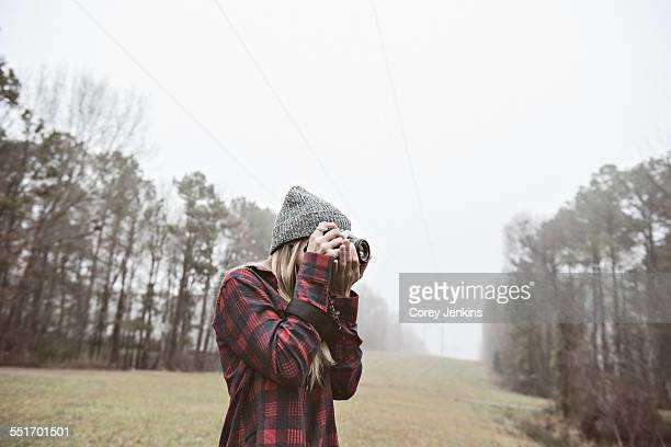 Young woman photographing in misty field