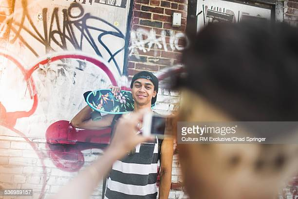 Young woman photographing skateboarder boyfriend with smartphone