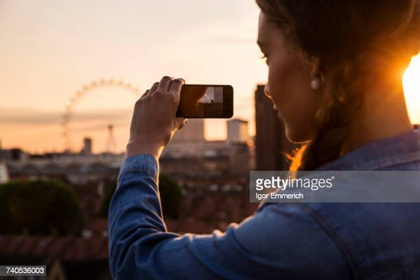 Young woman photographing skyline at sunset roof party in London, UK