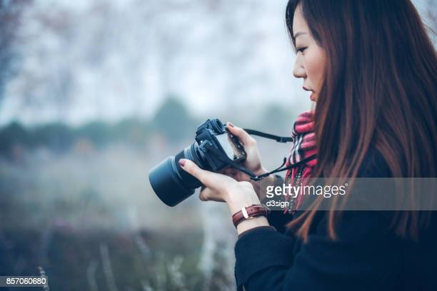 Young woman photographing the beautiful scenics with camera outdoors in a natural parkland