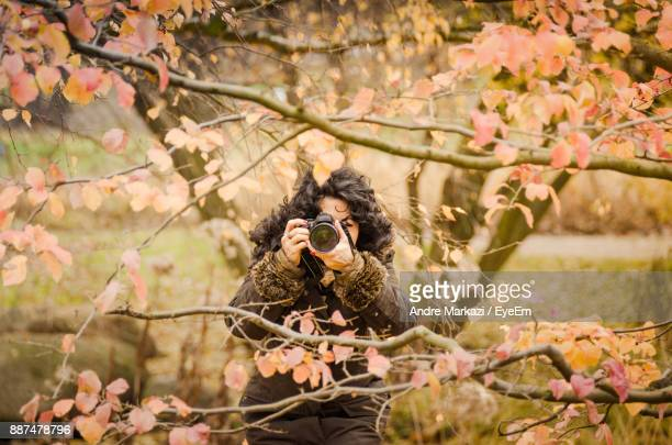 Young Woman Photographing While Standing In Forest