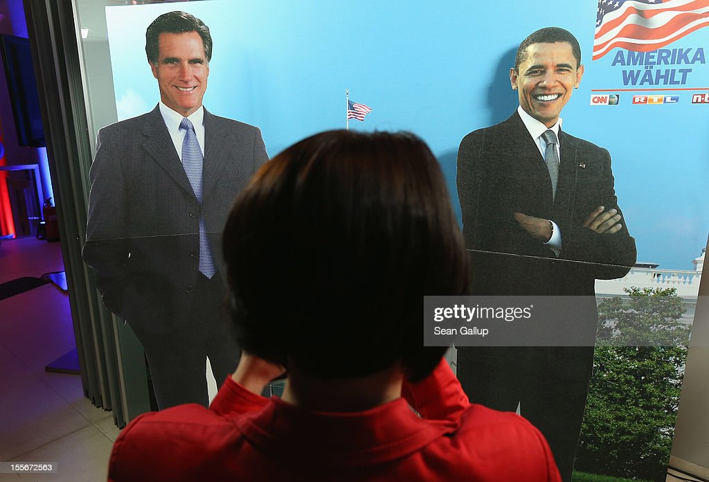 A young woman photographs cardboard figures of Mitt Romney (L) and <a gi-track='captionPersonalityLinkClicked' href=/galleries/search?phrase=Barack+Obama&family=editorial&specificpeople=203260 ng-click='$event.stopPropagation()'>Barack Obama</a> at a U.S. election party at the Bertelsmann Representation on November 6, 2012 in Berlin, Germany. Polls suggest today's voting in American presidential elections will create a neck and neck race between incumbent Democrat President <a gi-track='captionPersonalityLinkClicked' href=/galleries/search?phrase=Barack+Obama&family=editorial&specificpeople=203260 ng-click='$event.stopPropagation()'>Barack Obama</a> and his opponent, Republican Mitt Romney.