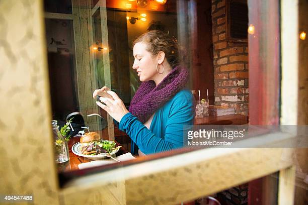 Young woman photographs her food with phone in cafe