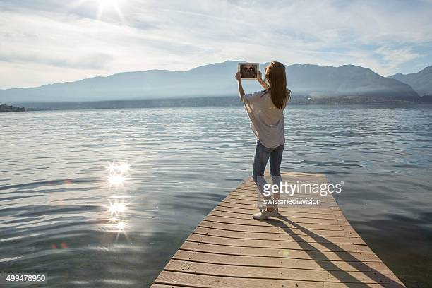 Young woman photographs landscape with digital tablet