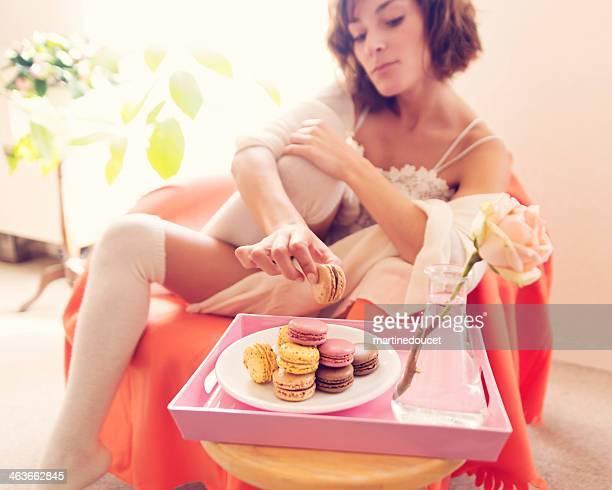 Jeune femme cueillir des macarons sur le plateau.