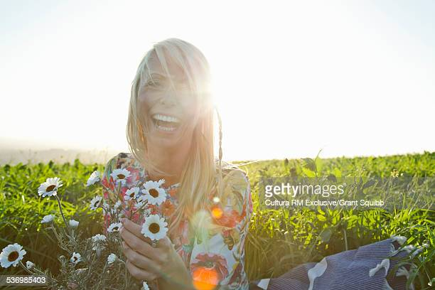 Young woman picking daisies whilst laughing