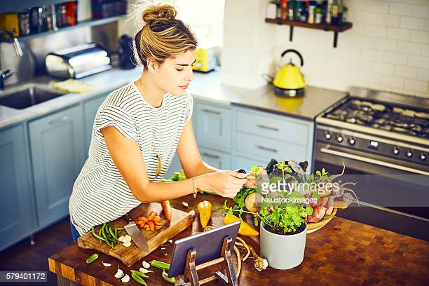 Young woman picking mint leaves at kitchen island